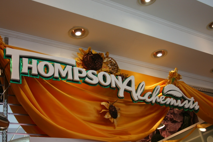 a Thompson Alchemists logo sign carved out of wood by Edd Fenner